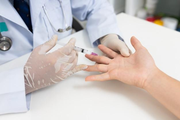 Aziatische arts of verpleegsterhanden met spuit die aan medische palm injecteren. carpaal tunnelsyndroom, artritis, neurologische ziekte concept. gevoelloosheid van de hand