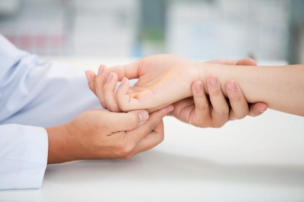 Aziatische arts onderzoekt patiënt met pols botproblemen pijnlijke pols veroorzaakt door langdurig werk op de laptop. carpaal tunnelsyndroom, artritis, neurologische ziekte concept. gevoelloosheid van de hand
