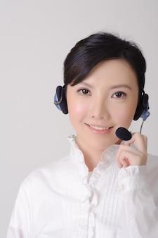 Aziatische assistent dame lacht en kijkt naar jou, close-up portret op grijze muur.