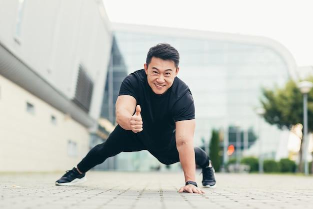 Aziatische atleet beoefent sport die van de grond duwt, kijkt naar de camera, glimlacht en toont duim omhoog