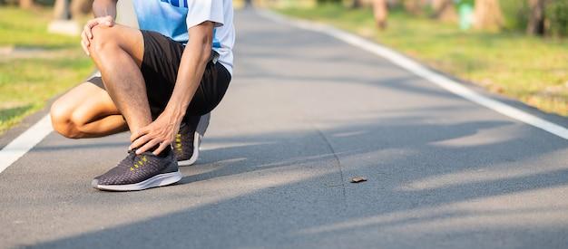 Aziatische atleet met enkelpijn en probleem na hardlopen en buiten oefenen