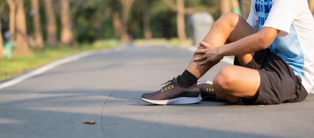 Aziatische atleet met kuitpijn en probleem na rennen en sporten buiten