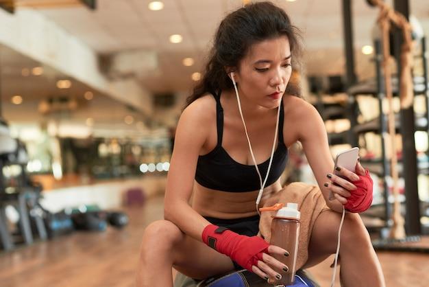 Aziatische atletische dame die onderbreking van training in gymnastiek nemen