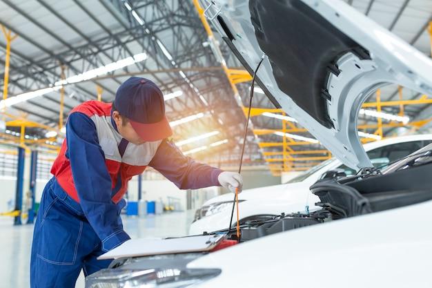 Aziatische auto-monteur gedetailleerde voertuiginspectie.