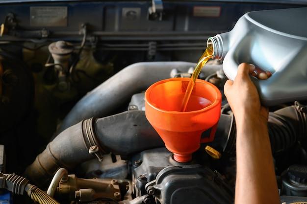 Aziatische automonteur werkt in autoreparatiewerkplaats giet olie voor olieverversing in de garage voor klanten die auto's repareren en olie verversen.