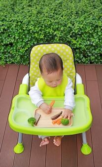Aziatische baby babyjongen eten door baby geleid spenen (blw). vinger eten concept.