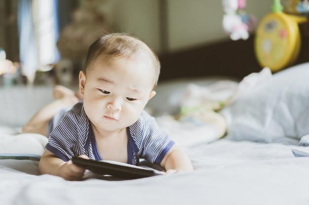 Aziatische baby is leren en kijken naar inhoud en sociale media op de mobiele telefoon.