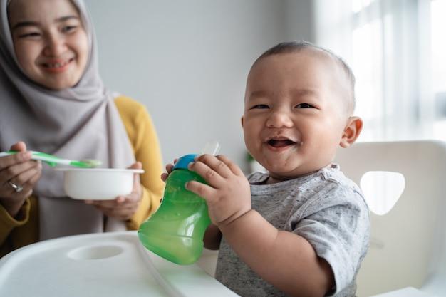 Aziatische babyjongen die aan camera glimlacht