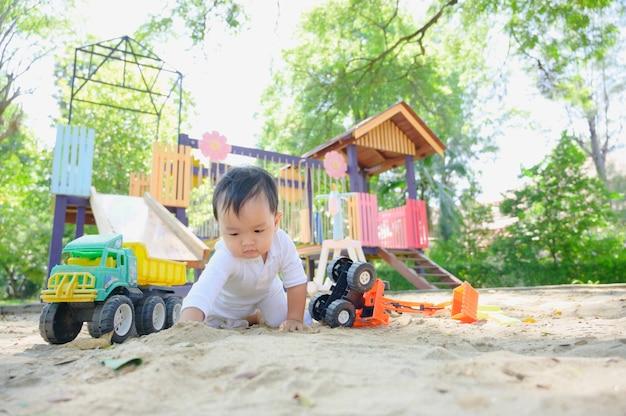 Aziatische babyjongen spelen met zand in een zandbak. gezonde actieve baby speelt buitenshuis speelgoed