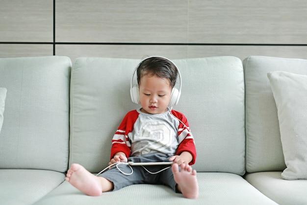 Aziatische babyjongenzitting op bank en het luisteren muziek bij hoofdtelefoons