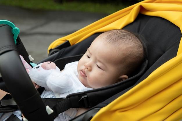 Aziatische babyslaap binnen wandelwagen