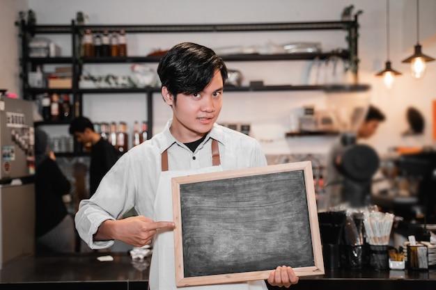 Aziatische barista die een bord vasthoudt en wijst als hij voor de pub staat