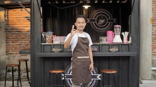 Aziatische barista die goed gebaart in café met containerthema