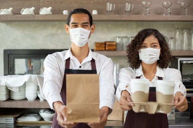 Aziatische barista met masker met papieren zak en koffiekopje voor klant om mee te nemen voor provent coronavirus in restaurant.