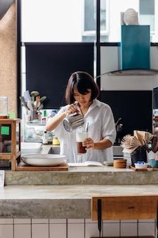 Aziatische barista-vrouw die schuim in bevroren cappuccinokoffie toevoegen.