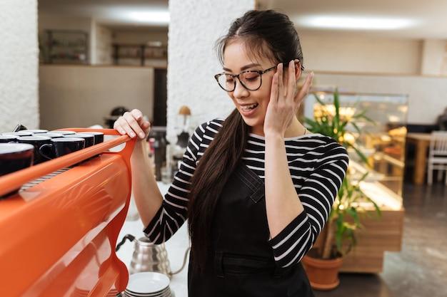 Aziatische barmeisje bij het koffiezetapparaat