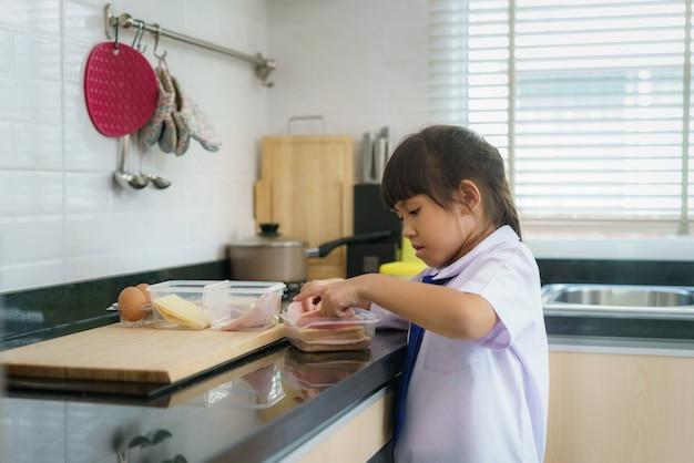 Aziatische basisschool student meisje in uniform sandwich maken voor lunchdoos in de ochtendschool routine voor dag in het leven klaar voor school.