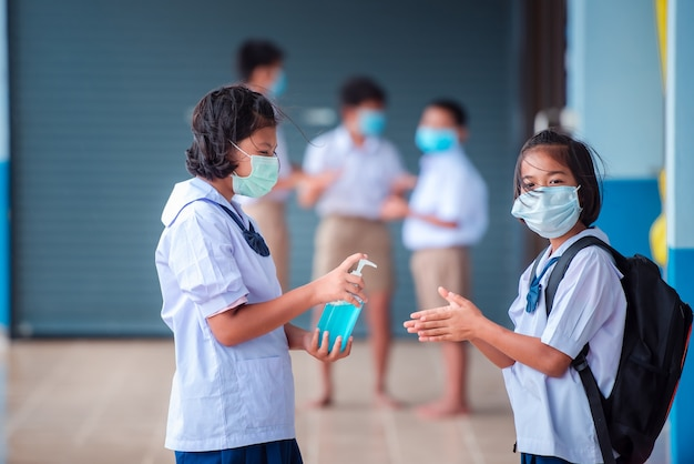 Aziatische basisschoolleerlingen draag een medisch masker om besmetting met het coronavirus te voorkomen