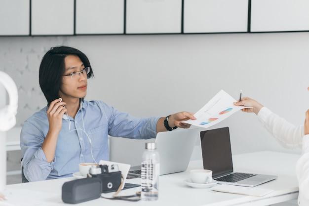 Aziatische beambte overhandigde documenten aan collega. indoor portret van brunette freelance programmeur in oortelefoons zitten met laptop en camera, terwijl het drinken van koffie.