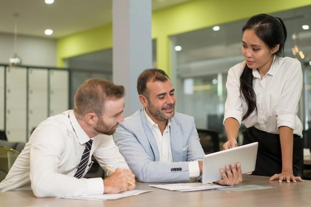 Aziatische bedrijfsdame die met medewerkers bij bureau werkt