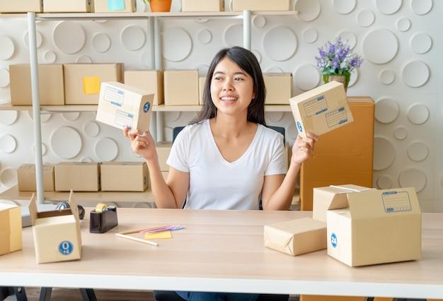 Aziatische bedrijfseigenaar die thuis met verpakkingsdoos op het werk werkt