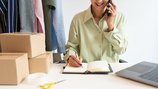 Aziatische bedrijfseigenaar die thuis werkt met de verpakking van haar online winkel, bereidt zich voor om producten aan klanten te leveren, alfa-generatie levensstijlconcept.