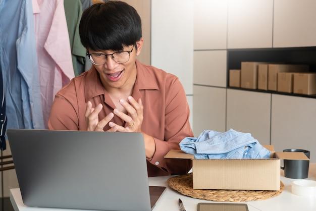 Aziatische bedrijfseigenaar die thuis werkt met de verpakking van zijn online winkel, bereidt zich voor om producten aan klanten te leveren, alfa-generatie levensstijlconcept.