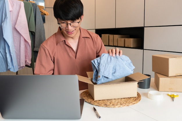 Aziatische bedrijfseigenaar thuis werken met verpakking van zijn online winkel voorbereiden om producten te leveren aan klanten, alpha generatie lifestyle concept.