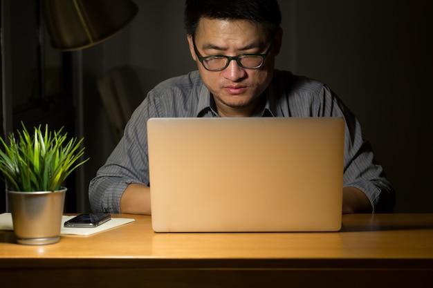 Aziatische bedrijfsmens die bij nacht werkt