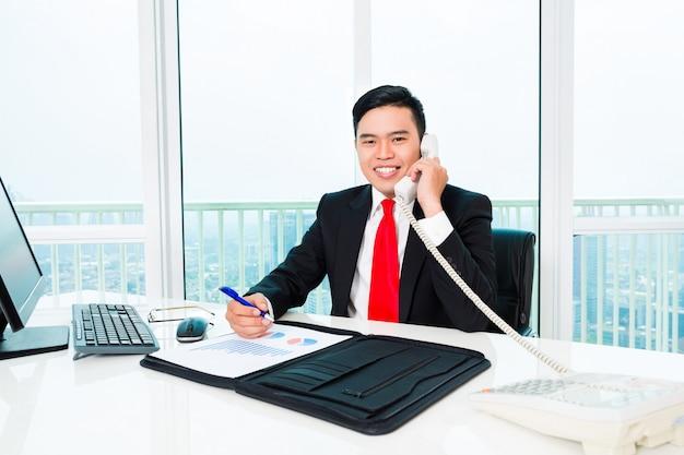 Aziatische bedrijfsmens die in bureau controlerende winst telefoneert