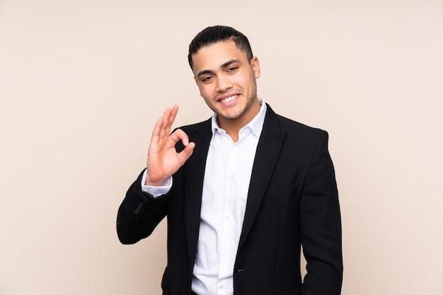 Aziatische bedrijfsmens die op beige achtergrond wordt geïsoleerd die een ok teken met vingers toont