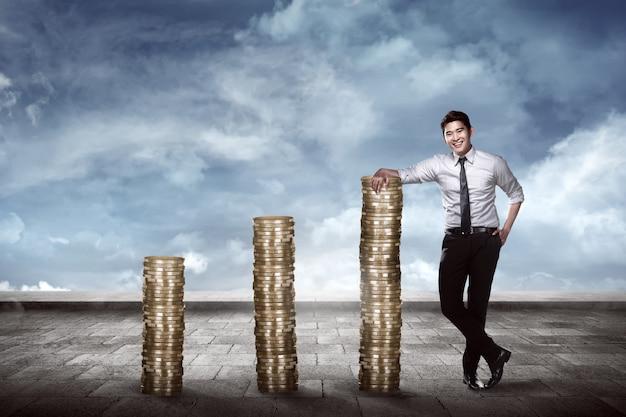 Aziatische bedrijfsmens die op de stapel van muntstukken leunt