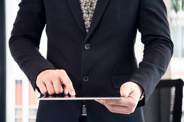 Aziatische bedrijfsmens die op kantoor met laptop glazenpen en documenten aan zijn bureau werken