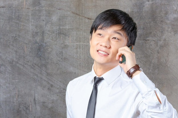 Aziatische bedrijfsmens die op mobiele celtelefoon spreekt