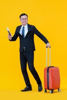 Aziatische bedrijfsmens met bagage klaar om voor reis te gaan