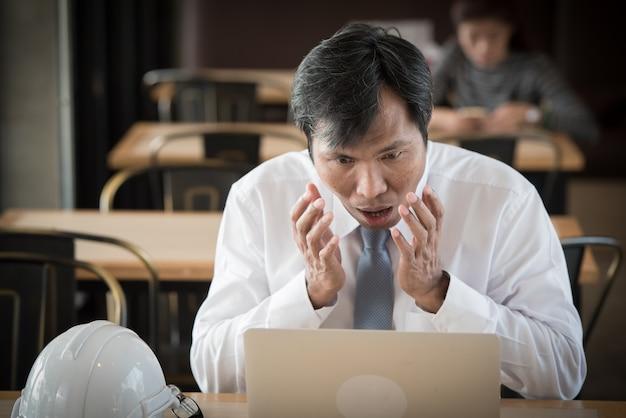 Aziatische bedrijfsmens met verrassingsgezicht voor laptop computer.