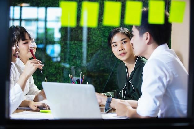 Aziatische bedrijfsmensen die aan project en brainstorming in bureau bij nacht samenwerken