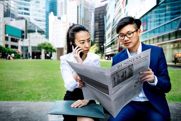 Aziatische bedrijfsmensen die de krant lezen