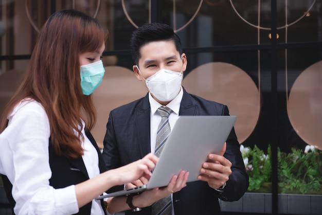 Aziatische bedrijfsmensen die met laptop aan openluchtplaats bedrijfsdistrict samenwerken