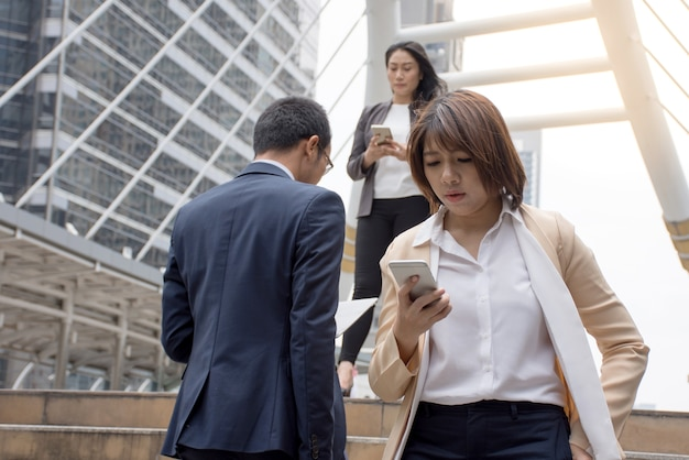 Aziatische bedrijfsmensen die mobiele telefoon houden en op een moderne gang lopen