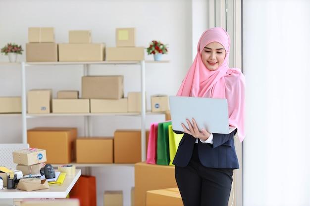 Aziatische bedrijfsmoslimvrouw die en computer bevindt zich met behulp van