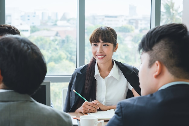 Aziatische bedrijfsvrouw die aan het team van de collegavergadering op kantoor luisteren de presentatie van de bedrijfs teamvergadering, conferentie plannings bedrijfsconcept
