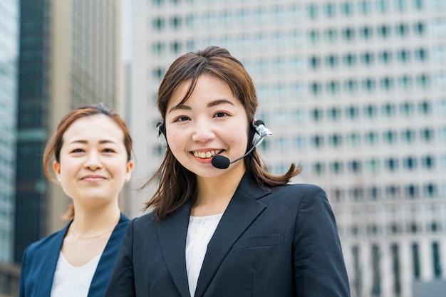 Aziatische bedrijfsvrouw die een hoofdtelefoon in bedrijfsdistrict draagt