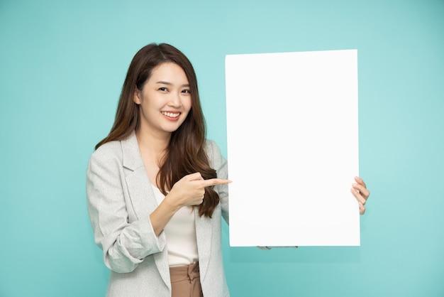 Aziatische bedrijfsvrouw die en leeg wit die aanplakbord toont houdt dat op groene achtergrond wordt geïsoleerd