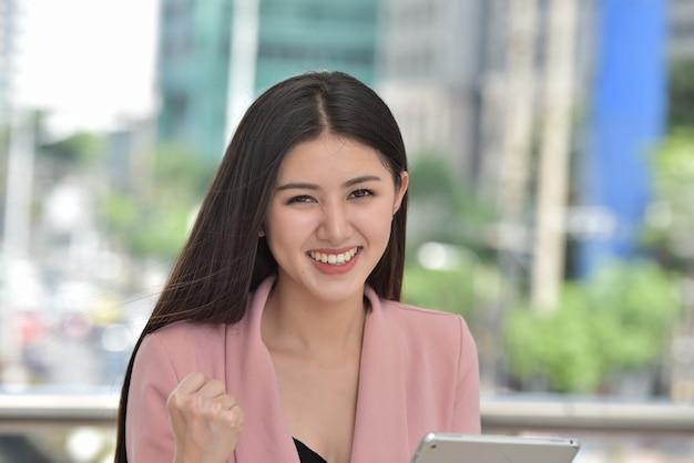 Aziatische bedrijfsvrouw die en zich aan camera met het aantrekkelijke glimlachen bevindt kijkt