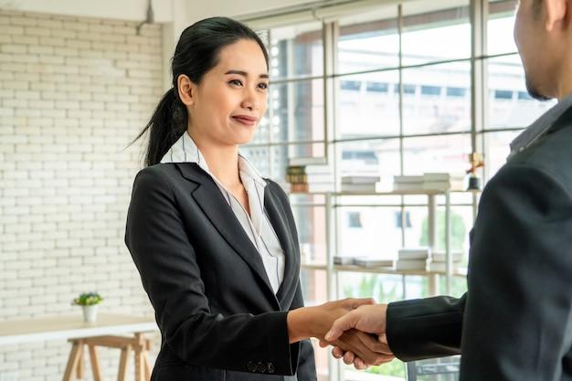 Aziatische bedrijfsvrouw die handen met haar partner schudden wanneer zij vergadering in bureau hebben gebeëindigd