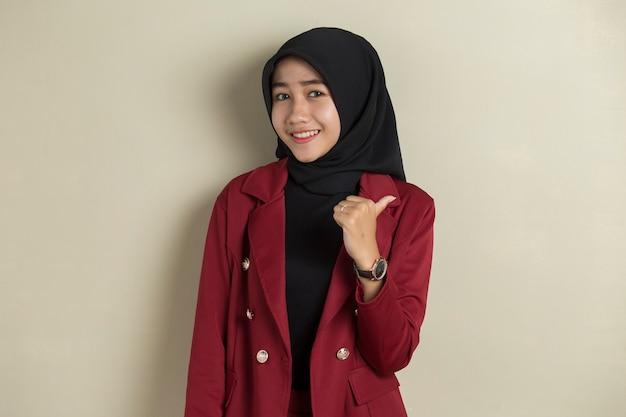 Aziatische bedrijfsvrouw die hijab met omhoog hand beduimelt ok draagt