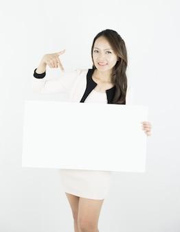 Aziatische bedrijfsvrouw die leeg aanplakbordaanplakbiljet houdt.