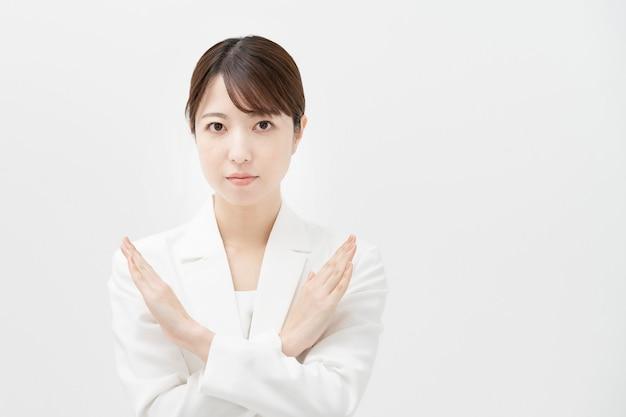 Aziatische bedrijfsvrouw die ng met beide handen en witte achtergrond ondertekent