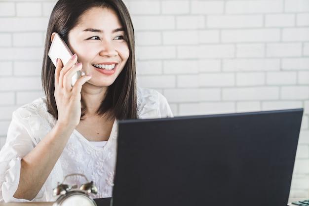 Aziatische bedrijfsvrouw die op slimme telefoon spreekt